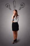 Den unga ladyen som är tänkande med, ifrågasätter markerar uppe i luften Royaltyfri Foto