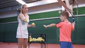 Den unga lagledaren undervisar pojken hur man slår tennisbollarna, medan utbilda på sportdomstolen Kvinnan kastar stock video