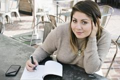 Den unga Latina kvinnlign skriver ner hennes 2019 nya år upplösningar arkivfoton