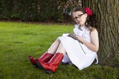 Den unga latinamerikanska flickan läser under träd Royaltyfri Fotografi