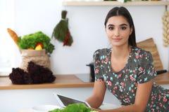 Den unga latinamerikanska kvinnan gör online-shopping vid den minnestavladatoren och kreditkorten Hemmafru funnit nytt recept för Royaltyfri Bild