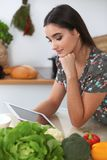 Den unga latinamerikanska kvinnan gör online-shopping vid den minnestavladatoren och kreditkorten Hemmafru funnit nytt recept för Royaltyfri Fotografi