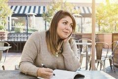 Den unga latinamerikanska kvinnan skriver ner hennes livmål i lyckligt le för tidskrift utomhus royaltyfria bilder