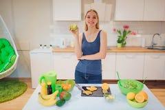 Den unga le blonda kvinnan rymmer det bet gröna äpplet, medan laga mat nya frukter i köket äta som är sunt arkivbild