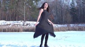 Den unga le brunettflickan som omkring vänder i svart klänning, sätter henne händer upp på en bakgrund för vinterskoglandskap arkivfilmer