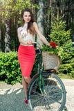 Den unga le kvinnan rider en cykel med en korg som är full av blomman Arkivbild