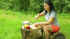 Den unga le kvinnan sitter på en stubbe på kanten av en skog och snittskivor av persikan för sallad på ett träbräde lager videofilmer