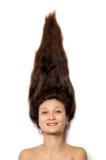 Den unga le kvinnan vänder mot med långt brunt hår arkivfoto