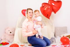 Den unga le modern sitter med den lilla dottern på händer i rum, Royaltyfri Foto