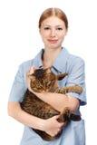 Den unga le veterinär- kvinnan som kramar vuxna människan, skrämde strimmig kattkatten Arkivbilder