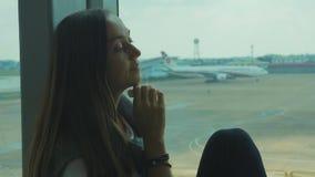 Den unga ledsna kvinnan gråter på flygplatsen med flygplanet på bakgrunden arkivfilmer