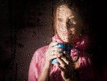 Den unga ledsna kvinnaståenden bak fönstret i regnet med regn tappar på den varm holding för koppdrinkflicka Royaltyfri Foto