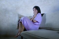 Den unga ledsna och deprimerade asiatiska kinesiska kvinnan som gråter den hemmastadda soffan för ensamt desperat sammanträde ouc arkivfoto