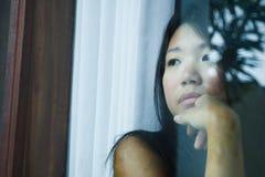 Den unga ledsna och deprimerade asiatiska kinesiska kvinnan som ser fundersam till och med lidande för fönsterexponeringsglas, sm arkivfoton