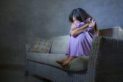 Den unga ledsna och deprimerade asiatiska koreanska kvinnan som gråter ensam desperat och bekymrat smärtar in, sittande hemmastat royaltyfria foton