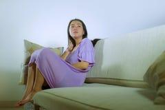 Den unga ledsna och deprimerade asiatiska koreanska kvinnan som gråter ensam desperat och bekymrat smärtar in, sittande hemmastat royaltyfri foto