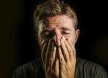 Den unga ledsna och skövlade mannen som gråter den desperata beläggningframsidan med hans händer som känner sig stressat och bort arkivbilder