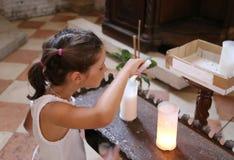 Den unga lilla flickan tänder en stearin in i kyrkan Arkivbild