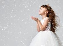 Den unga liten flickamodellen i den vita nattvardsgångvinterklänningen står i guld- krona med dyra ädelstenar Arkivfoto