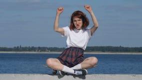 Den unga ljust rödbrun flickan jublar i seger stock video