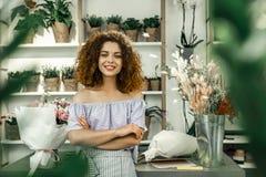 Den unga lockande studenten som tycker om hennes deltids- jobb i stort blom-, shoppar royaltyfri fotografi