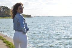 Den unga lockiga kvinnan med sexiga bakdelar near sjön Fotografering för Bildbyråer
