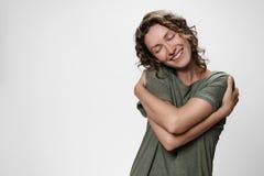 Den unga lockiga kvinnan som kramar sig, ser lycklig, uttrycker naturliga positiva sinnesrörelser arkivbild