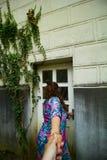 Den unga lockiga kvinnan står med henne tillbaka till kameran Royaltyfria Foton