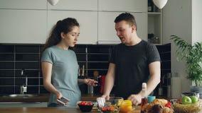 Den unga lockiga kvinnavisningen något som är otrevlig i telefon för make` s, medan han lagar mat, ropar de och stock video