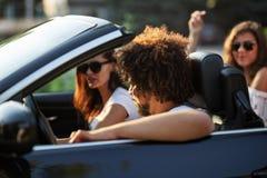 Den unga lockiga mörkhåriga mannen och två härliga mörker-haired flickor i solglasögon sitter i en svart cabriolet royaltyfria foton
