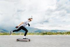 Den unga Longboarderen skjuter hans fot ut på hans longboard över landsvägen arkivfoton