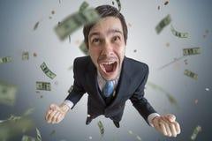 Den unga lyckade affärsmannen är en vinnare Pengar faller från över royaltyfria foton
