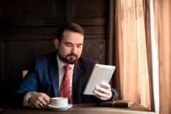 Den unga lyckade affärsmannen läser nyheterna på minnestavlan royaltyfria foton