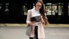Den unga lyckade brunettaffärskvinnan går till och med staden med dokument och räknar legitimationshandlingar stock video