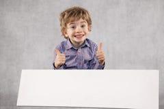 Den unga lyckliga affärsmannen rekommenderar ett ställe för annonsering, kopia royaltyfri fotografi