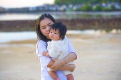 Den unga lyckliga asiatiska kinesiska kvinnamodern av förtjusande behandla som ett barn flickan som rymmer hennes söta lilla dott arkivbild