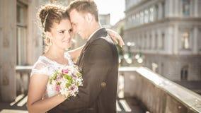 Den unga lyckliga bröllopparbruden möter brudgummen på en bröllopdag Lyckliga nygifta personer på terrass med ursnygg sikt Royaltyfria Foton