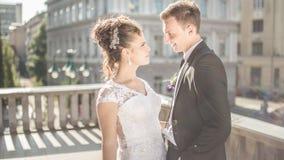 Den unga lyckliga bröllopparbruden möter brudgummen på en bröllopdag Lyckliga nygifta personer på terrass med ursnygg sikt Royaltyfria Bilder