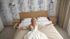 Den unga lyckliga bruden hoppar på säng stock video