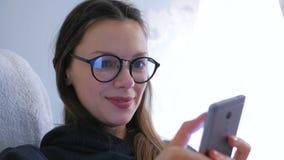 Den unga lyckliga brunettkvinnan i exponeringsglas skriver ett meddelande p? en mobiltelefon arkivfilmer