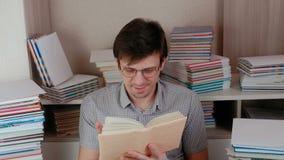 Den unga lyckliga brunettmannen sätter på hans exponeringsglas och läsning en bok lager videofilmer