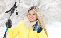Den unga lyckliga caucasian kvinnan med skidar poler på den utomhus- vintern Royaltyfria Bilder