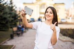 Den unga lyckliga caucasian kvinnan som bär tillfällig kläder, tar en selfie med hennes smartphone på stadsgatorna arkivbild