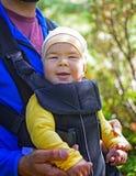Den unga lyckliga faderhållen behandla som ett barn pojken som 7 månader på baksida behandla som ett barn in att gå för bärare royaltyfri foto