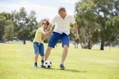 Den unga lyckliga fadern och upphetsade lite 7 eller 8 år gammal son som tillsammans spelar fotbollfotboll på stad, parkerar träd arkivfoton