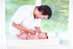 Den unga lyckliga fadern som spelar med hans nyfött, behandla som ett barn sonen Royaltyfria Bilder