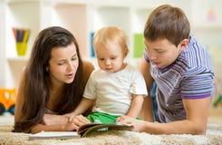 Den unga lyckliga familjen med behandla som ett barn läs- barn för pojke Arkivbilder
