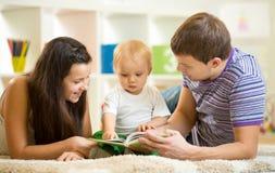 Den unga lyckliga familjen med ungepojken läste barnboken Fotografering för Bildbyråer