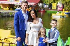 Den unga lyckliga familjståenden på bakgrund av hösten parkerar Arkivbild
