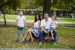 Den unga lyckliga familjståenden på bakgrund av hösten parkerar Arkivfoto